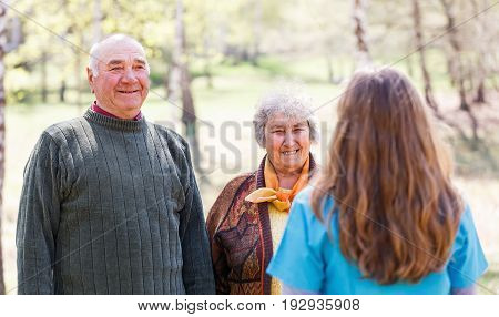 Photo of elderly couple and young caregiver