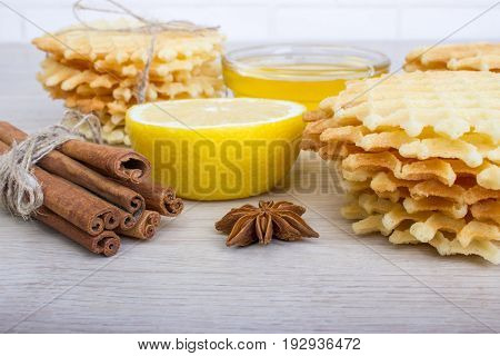 Waffle with badian cinnamon honey lemon on a light wooden background.
