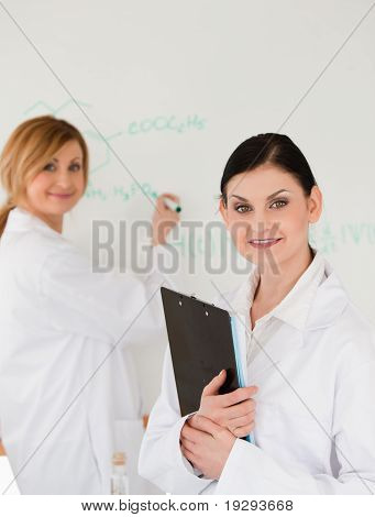 Two scientists posing and writing a formula on a whiteboard