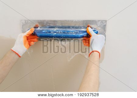 Worker's hands are plastering a wall in a apartment.