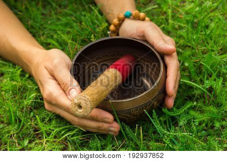 The Hands Of A Young Woman On Tibetian Singing Bowl With Wooden Stick On The Grass.
