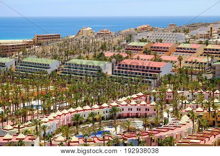 MORRO JABLE SPAIN - JUNE 25 2017: Hotel resorts with green palm trees around and view on the Atlantic ocean in Morro Jable on the Canary Island Fuerteventura Spain.