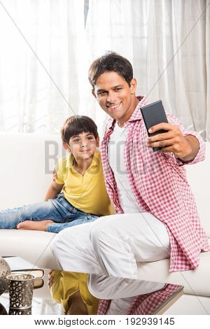 Family time - Indian father taking selfie picture with son or little boy while sitting on a sofa, indoors. Selective focus