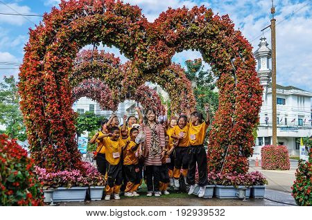 CHIANG RAI, THAILAND - DECEMBER 24, 2012: Group of children stantding under a flower heart in the city of Chiang Rai Thailand