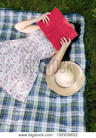 Woman reading a book and covering face outside in the grass