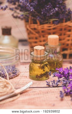 Fresh lavender oil with fresh flowers on wooden background