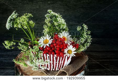 Wicker color white with red basket with a snowball and a field of small white flowers and chamomile . Wooden background rustic style. A horizontal frame.