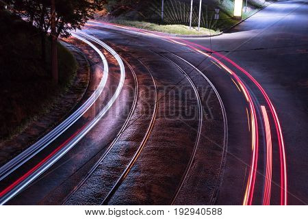 Bend of the road with tram rails in the light of street lamps with a trace from the lights of passing cars