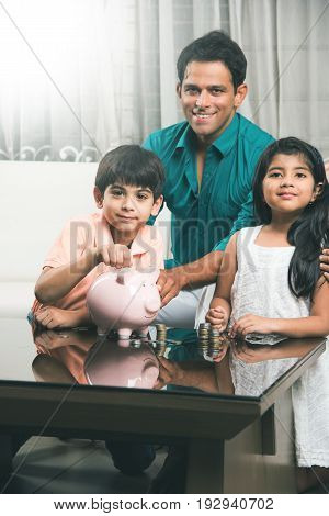 Happy indian father and two kids with piggy bank and indian currency coins