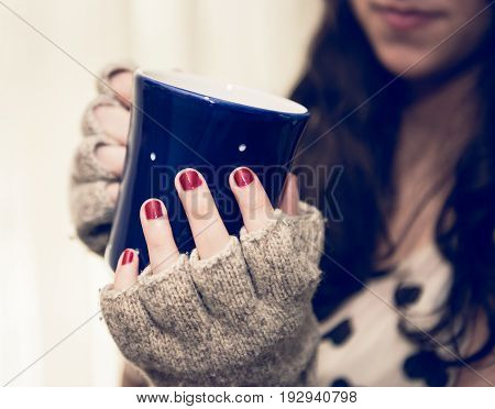 Woman relaxing and holding a cup of coffee or tea.  Morning start concept.