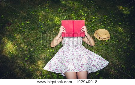 Woman reading a book and covering face outside on the grass