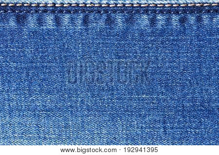 External Seams Yellow And Blue Colors On Jeans Fabric Macro Close Up. Texture And Background.