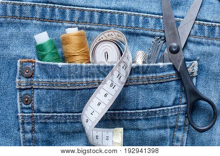 Seam Ripper Thread Centimeter Tape Thimble Pins Scissors In Pocket Of Blue Jeans On White Background Close Up.