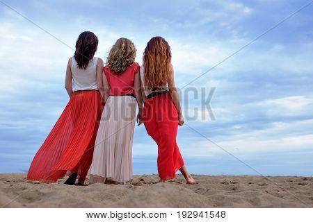 Young women in a long dress standing on the beach in summer evening. Friendship between girls