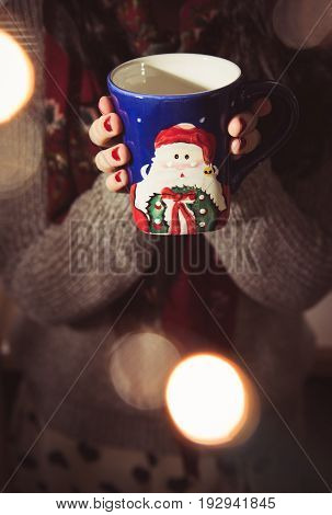 Woman drinking coffee/tea/hot chocolate during the Christmas season out of a Santa Claus mug