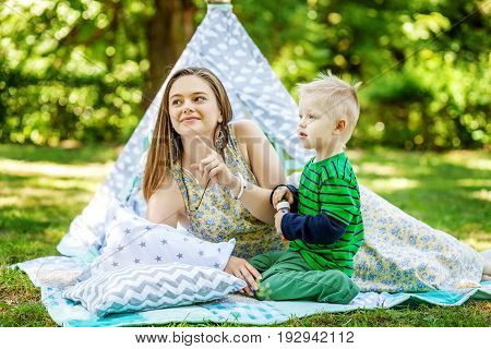 Happy mother and little son in the park. The concept of lifestyle and childhood.