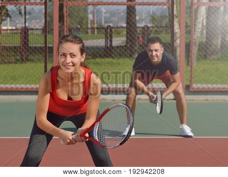 Couple playing doubles at the tennis court. Waiting for second serve. Healthy fitness concept with active lifestyle.