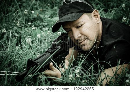 The man holding a gun k44 and shooting at afternoon, to a target recumbent on the green grass, small depth.