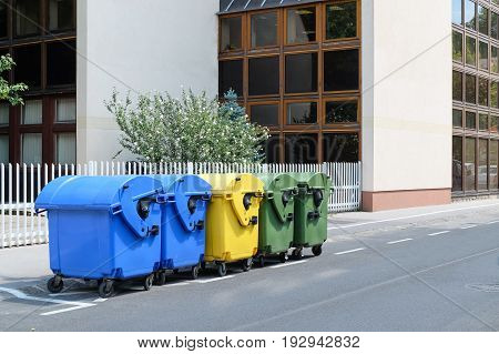 Five plastic recycling bins outdoors. Perspective shot.
