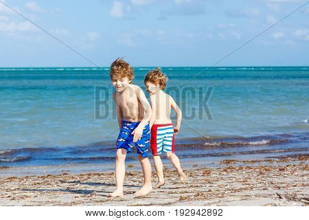 Two little kids boys having fun on tropical beach, happy best friends playing with sand, friendship concept. Siblings brothes in swim trousers. Key Biscayne, Miami, Florida.