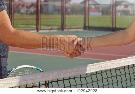 Young players shaking hands on tennis court, only hands can be seen. Healthy fitness concept with active lifestyle.