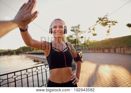 Runner girl giving high five in the park.