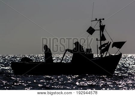 Fishermen at sea in a small fishing boat. Peaceful silhouette by moonlight before dawn. Moonlit water glistening as boat manoeuvres to fish.