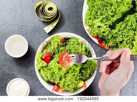 Hand With Fork Over White Ceramic Bowl Of Delicious Salad Of Cucumbers And Tomatoes And Vegetables O