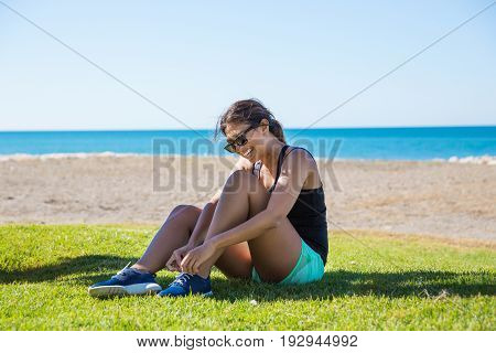 Young Happy Sportswoman Sitting On Grass Tying Shoelaces