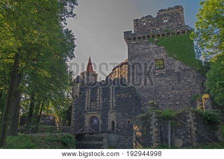 The photo shows the historic castle Grodziec located in south-western Poland. You can see the general outline of the castle from the outside, the ramparts, the gate with wooden bridge, the defensive tower on the right and the left bay and the tower. Aroun
