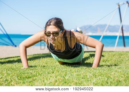 Young Pretty Sportswoman Doing Push-ups On Grass