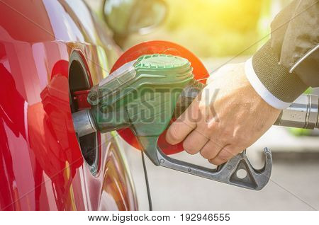 Male hand holding green pump filling gasoline