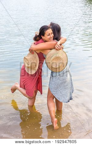 Two friends hugging each other in water