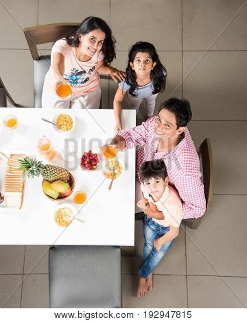 Top view of happy, smiling Asian Indian family of mother, father, son and daughter eating healthy food & salad at a dining table. Indians eating breakfast, lunch or dinner. Top view, Selective focus