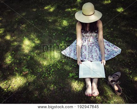 Woman reading a book outside on the grass on a sunny day