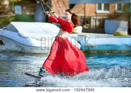 Woman in a red dress skates on a wakeboard.