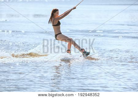 Woman in a swimsuit rides on wakeboarding around splashes of water.