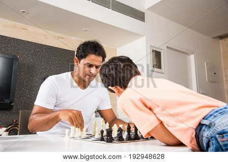 Indian father playing chess with son, Asian father and son playing indoor game called chess while sitting on table. Selective focus