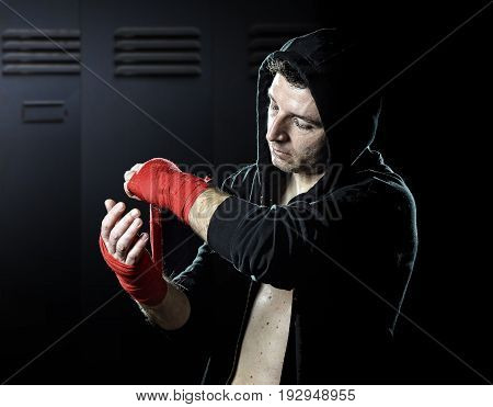 young man in boxing hoodie jumper with hood on head wrapping hands and wrists getting ready for fighting posing concentrated isolated on gym locker room background