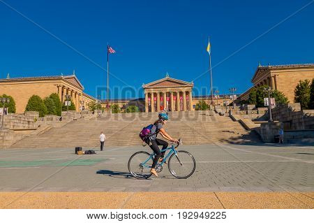 PHILADELPHIA, USA - NOVEMBER 22, 2016: Unidentified woman biking in front of Museum of Art East entrance and North wing buildings and empty main plaza with Greek revival style facade.
