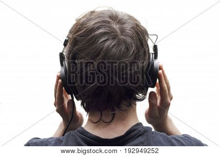Rear view closeup of young man listening to music with stereo headphones on white background.