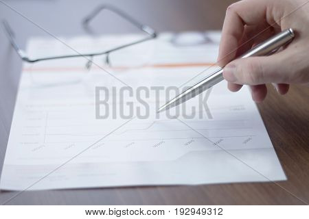 Business chart stiill life with glasses and a hand holding a pen.