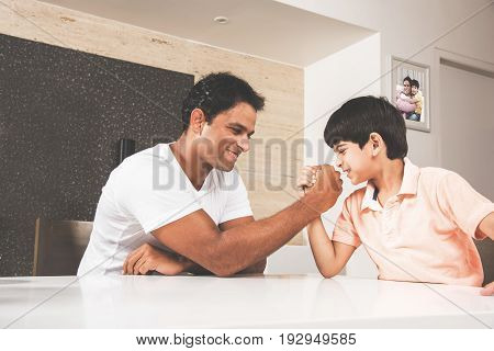 Family time - indian young father playing or competing in arm wrestle or wrestling with cute son at dining table