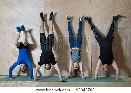 People Handstand push-up workout at gym, pushups updide down near the wall