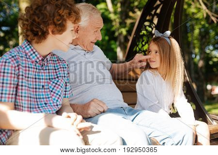 Funny moment. Positive delighted man wrinkling his forehead and keeping smile on his face while touching nose of his granddaughter