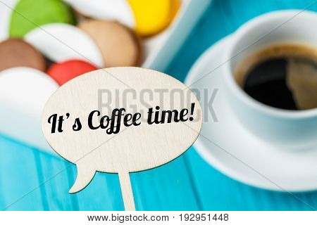 Inscription on wooden topper against background of macaroons and coffee