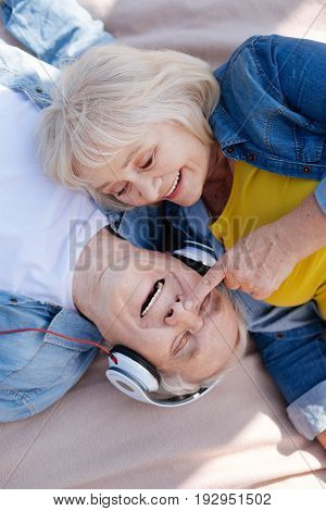 Listen to music. Attractive woman keeping smile on her face and touching nose of her husband while flirting with him