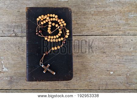 The book of Catholic Church liturgy and rosary beads on the wooden table