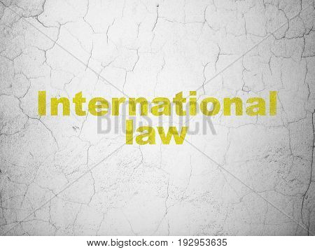 Politics concept: Yellow International Law on textured concrete wall background
