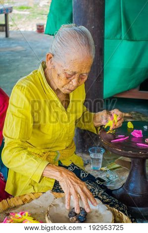 BALI, INDONESIA - MARCH 08, 2017: Old woman preparing an Indian Sadhu dough for chapati on Manmandir ghat on the banks of the holy river Ganges in Varanasi.